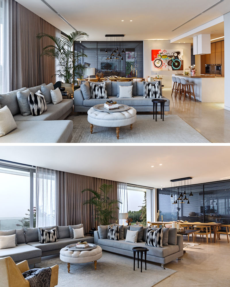 This modern living room is beside floor-to-ceiling windows and has a grey couch with bold pattern throw pillows, a light grey carpet on the concrete floor defines the area.