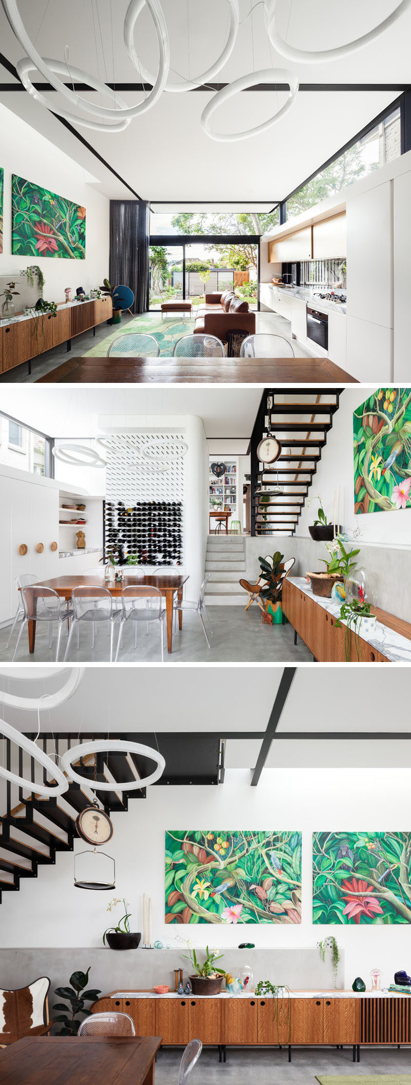 Inside this modern house, the living room, kitchen and dining room share the same space, with the light wood kitchen running alongside one wall. A wall of wine near the dining table and chairs doubles as a piece of art, while black beams break up the all white ceiling, and match the stairs at the end of the room.