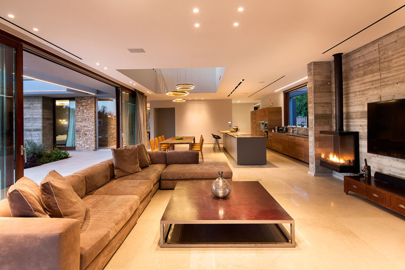 Inside this modern home, the living room shares the space with the dining room and kitchen. To allow the breeze from the Mediterranean Sea to filter into the house, there are plenty of wood framed sliding glass doors that can be opened.