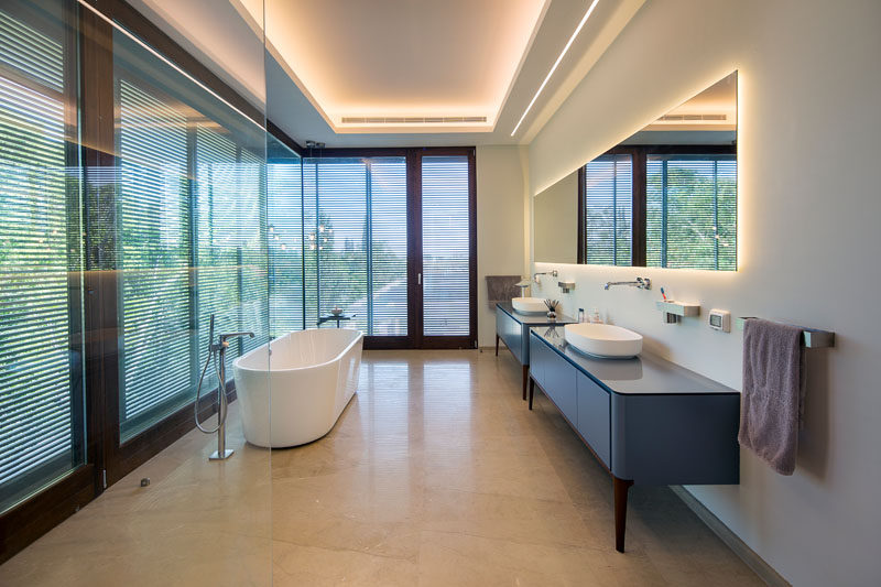 In this modern master bathroom, lighting is hidden from view in the ceiling and behind the large rectangular mirror. Double vanities provide plenty of space and a white freestanding bathtub sits next to floor-to-ceiling windows with privacy screens.