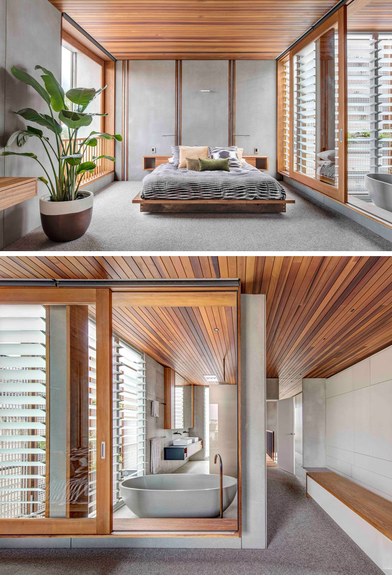 This master bedroom, minimal in its design, has large walls of windows that open to let a cross breeze through. The wood ceiling continues from the bedroom through to the ensuite bathroom that's separated by a large sliding glass window.