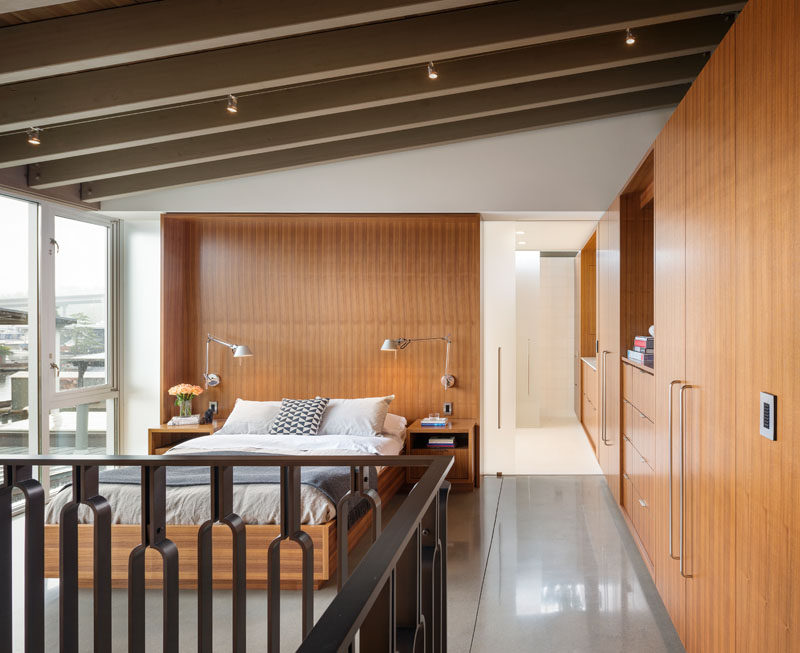 In this modern and open master bedroom, wood cabinets and closets line the wall and opposite is a wall of windows. Wood is also used as a feature headboard and as the frame for the bed.