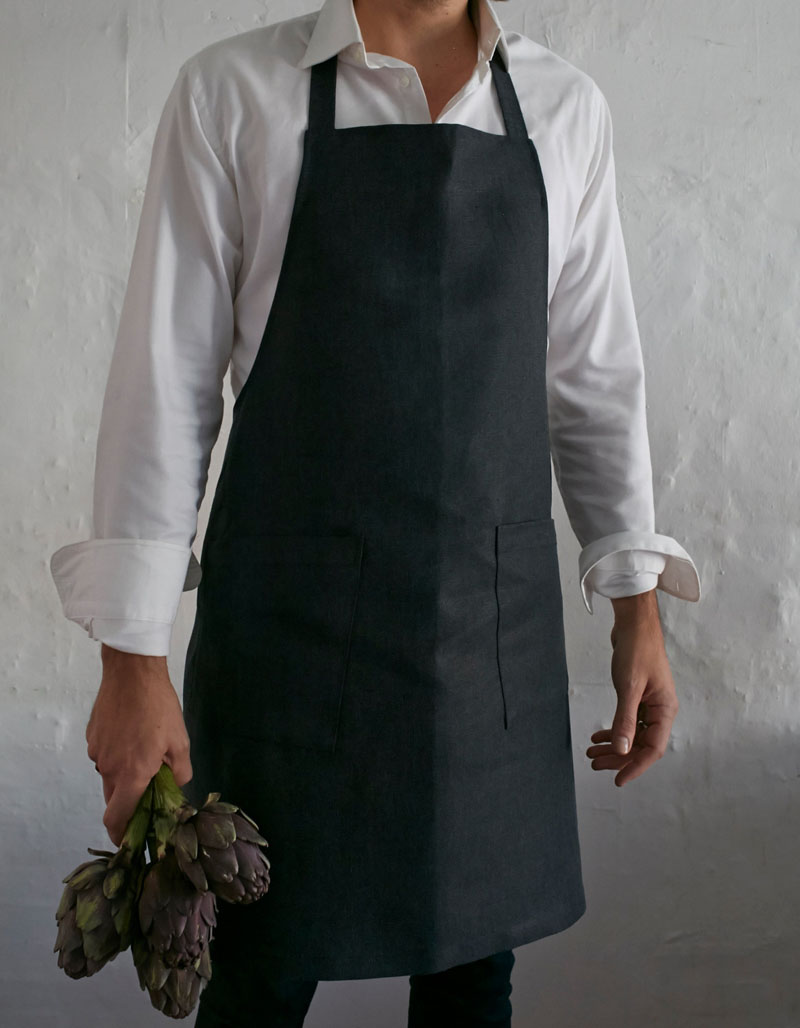 This modern black apron adds style to both the kitchen and the chef, and helps keep things from getting too messy in the kitchen.