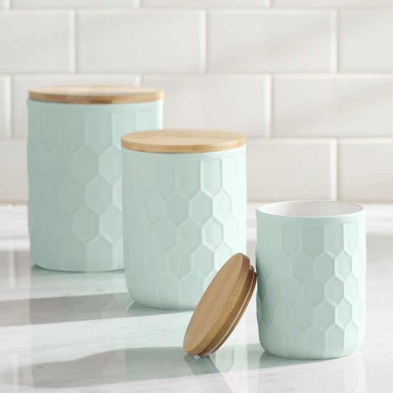 Topped with a bamboo lid to stow various goods, these modern mint colored canisters have a honeycomb inspired pattern making them easy to hold. #PantryIdeas #StorageIdeas #KitchenStorage #KitchenJars #ModernJar #ModernCanister #PantryJars