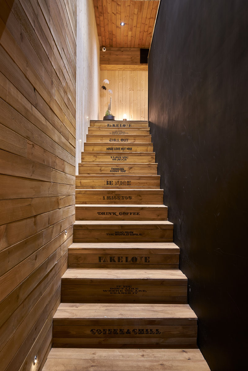 "In between black and wood walls in this modern coffee shop, is a set of wood stairs stamped with sayings like ""Be Nice"" and ""Chill Out"", lead to the upper level of this coffee shop."