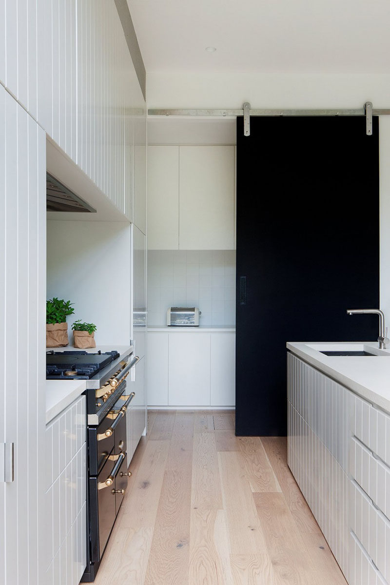 The black sliding barn door in this modern kitchen creates a bold contrast against the all white cabinetry and light wood flooring.