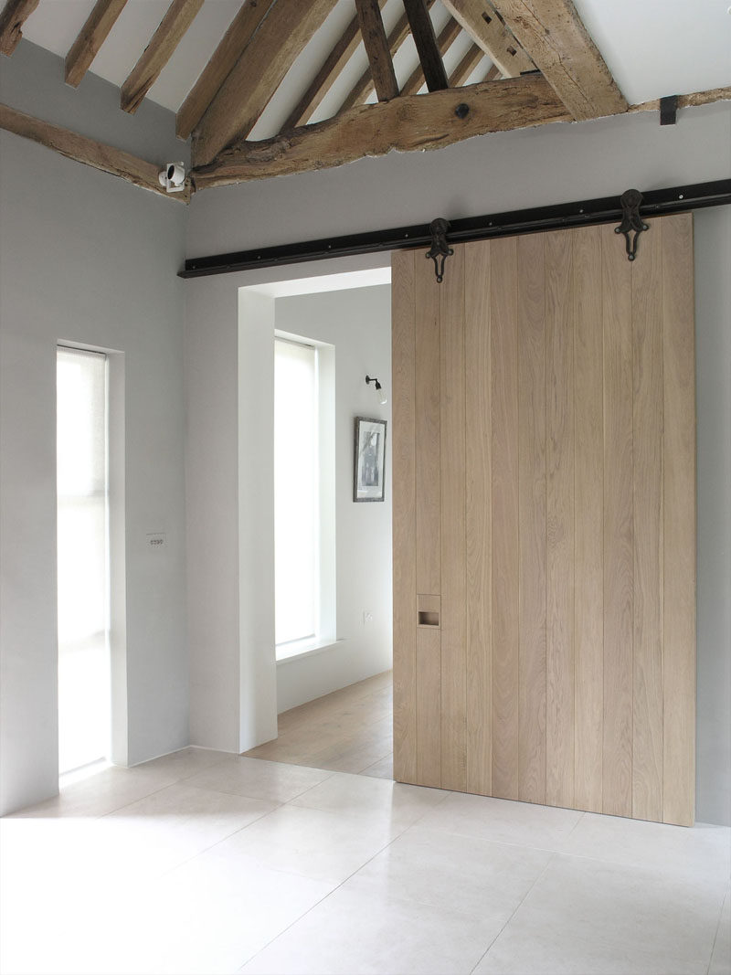 This large sliding barn door made from light wood and a dark metal rail creates a contemporary look in this remodeled home that maintained some of the original rustic ceiling details.