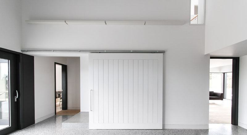 The White Sliding Barn Door In This Modern Home Helps Keep The Space Bright  And Welcoming, And Blends In With The White Walls Around It.