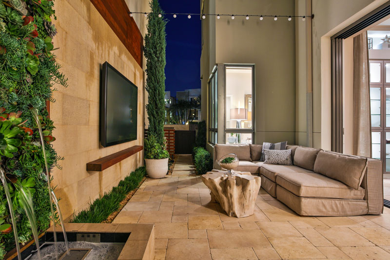 The narrow space on this modern patio is tight but it still manages to comfortably fit a barbecue, a large sofa, a water feature, and a wall mounted TV.