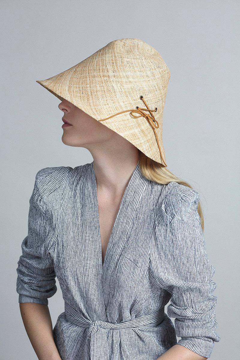Yael Cohen, a fashion designer based in Israel, has created a line of modern straw hats that are perfect for summer, like this modern light colored straw bucket hat that has a lace detail on it.