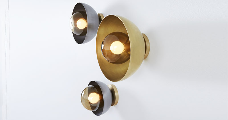 These modern metallic wall sconces are made from hand blown glass, with a steel or brass cover.