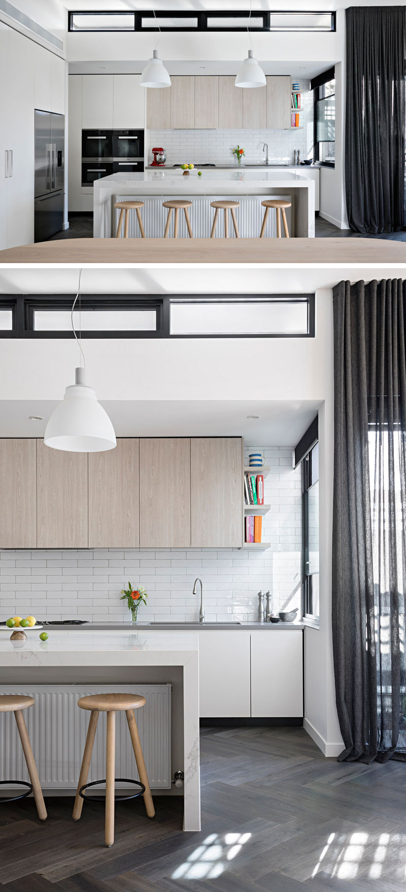 The modern kitchen has a large white island that sits below two pendant lamps. White rectangular tiles have been used as a backsplash, below light wood cabinets.