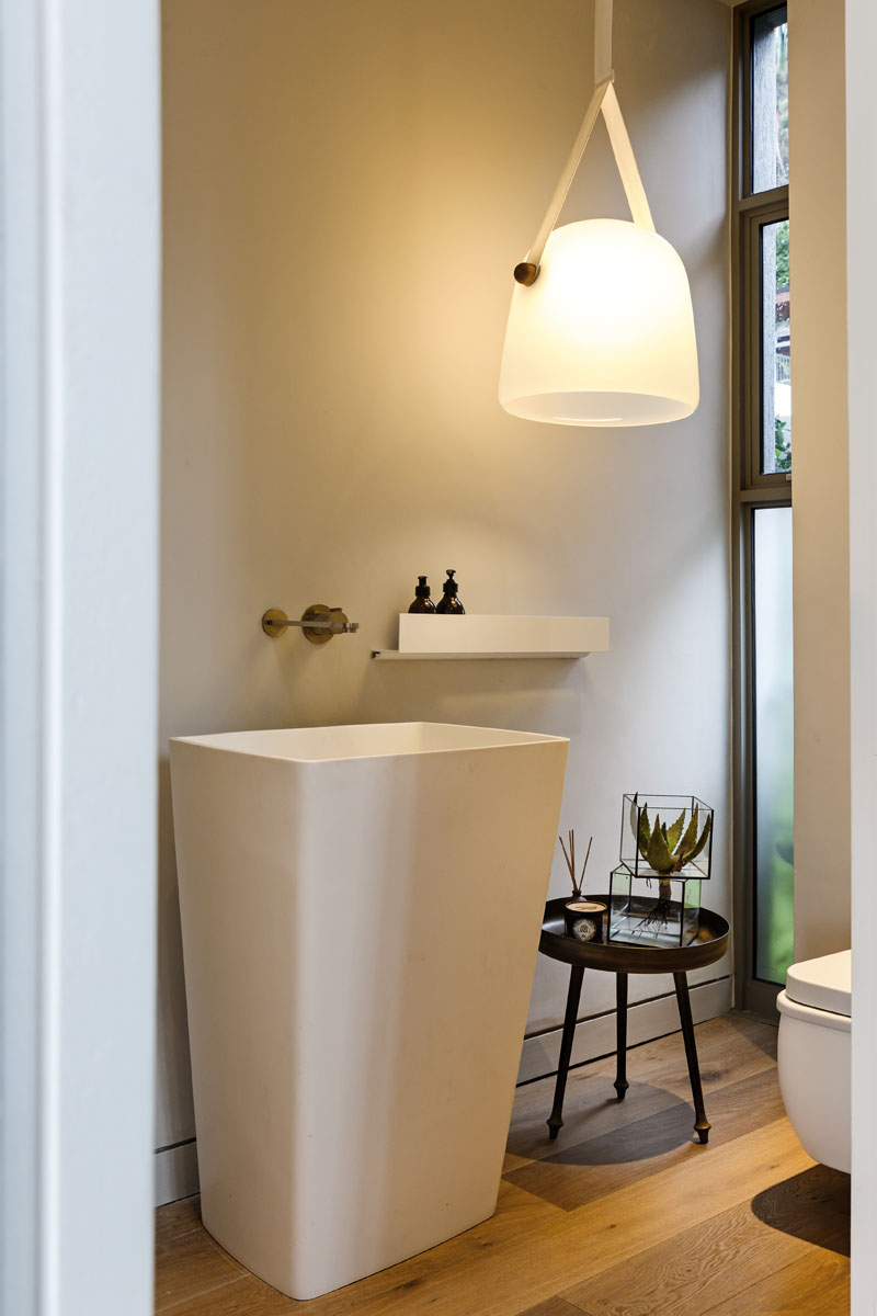 This modern bathroom has an oversized white pendant light, and a large white stand alone sink beside a set of windows.