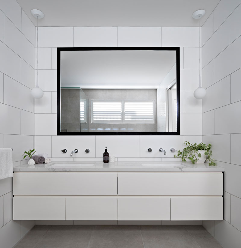 A large black framed mirror stand outs in this white modern bathroom that features large rectangular tiles on the walls . Two white pendant flank the mirror and hang above a marble counter with dual sinks.