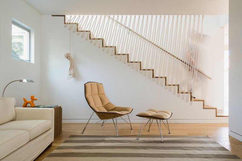 These modern stairs have a rope safety barrier along one side of the stairs and a metal railing on the other side, making sure that these white and wood stairs are safe and chic at all times.
