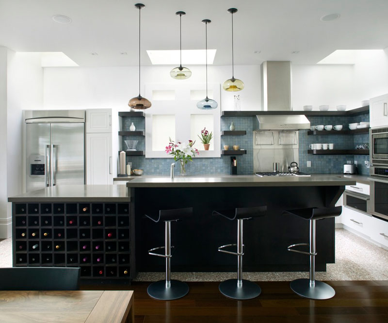 A large black, built-in storage unit for wine sits below the long grey island in this modern kitchen.