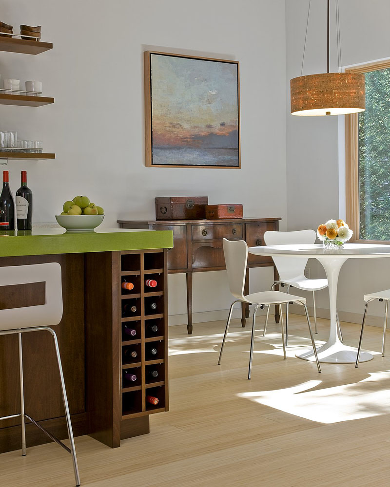 Wine can be stored below this modern green and dark wood island.