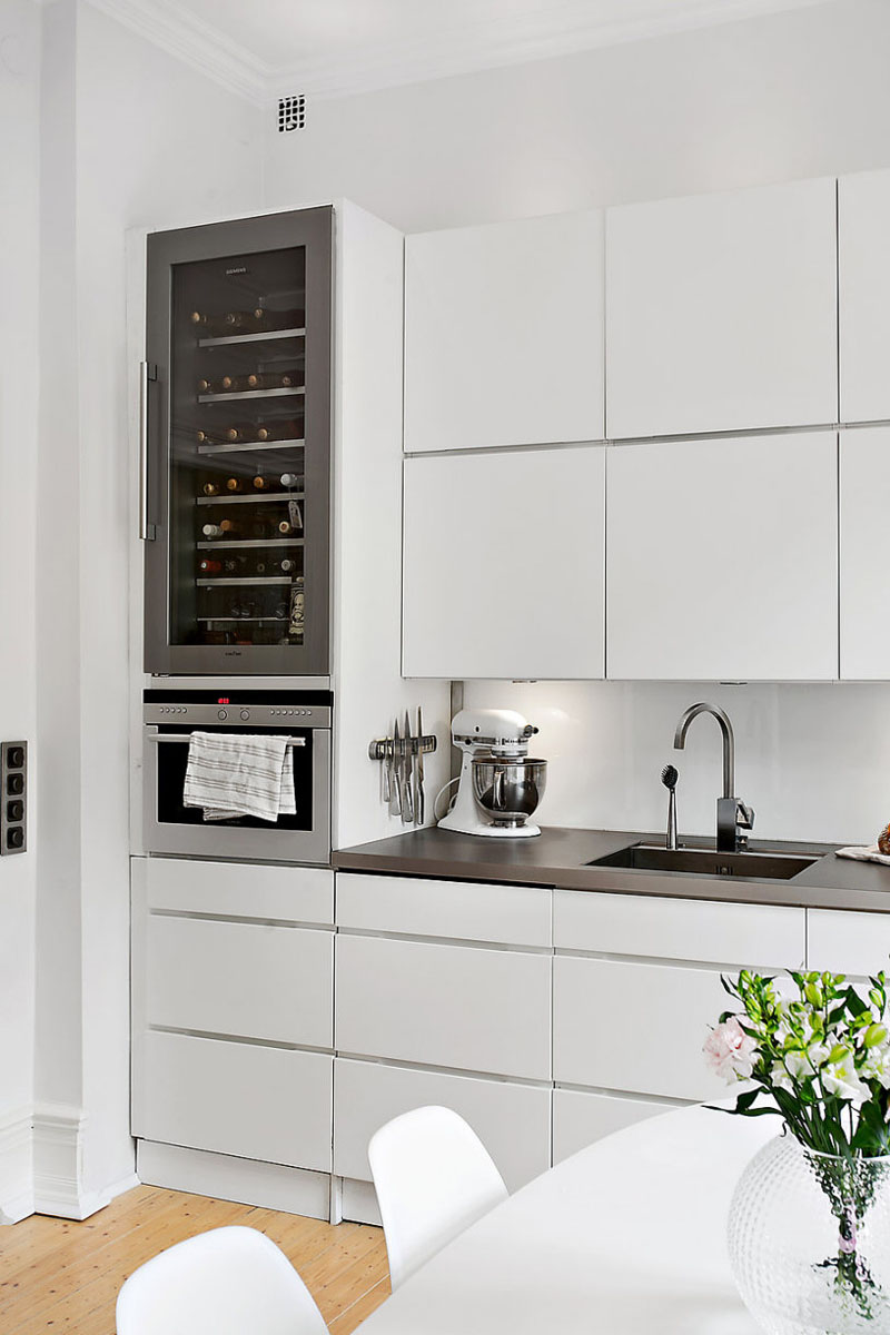 This Modern Wine Fridge Sits Above The Counter And Beside The White Cabinets .
