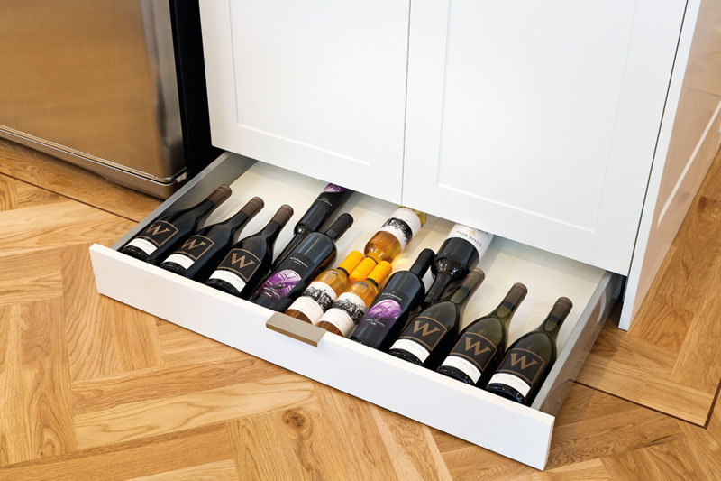 This modern toe kick drawer for wine storage is easily accessed below the white cabinets.