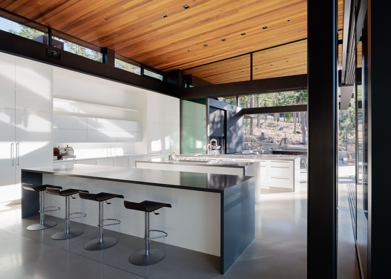This modern kitchen that consists of three large white islands with grey countertops. The stained cedar ceiling stands out above the concrete floor, while white cabinetry sits below a set of clerestory windows, providing even more light to the open space.