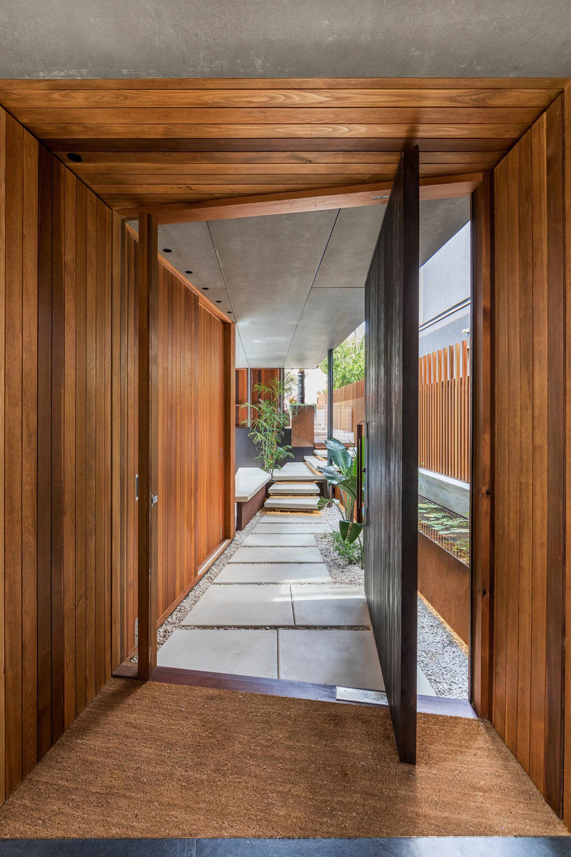 A small path leads from the front of the house to the large pivoting wood front door that sits on an angle.