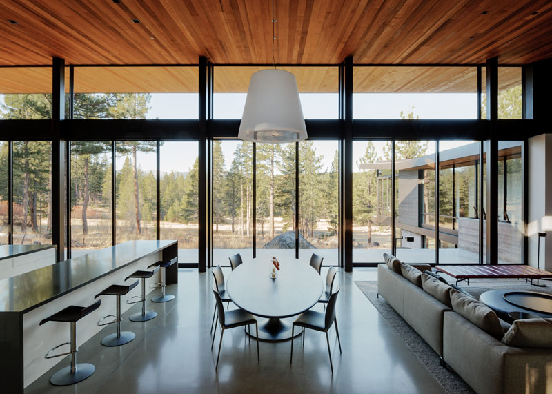 An oval dining table sits below a large white pendant light, and separates the kitchen from the living room. Floor-to-ceiling glass walls give an expansive view of the terrain outside while eating.