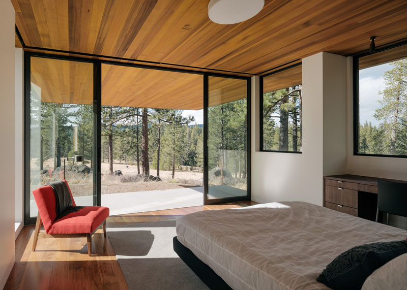 This modern bedroom located on the lower floor of the house, has large sliding glass doors that open up to a small private patio.