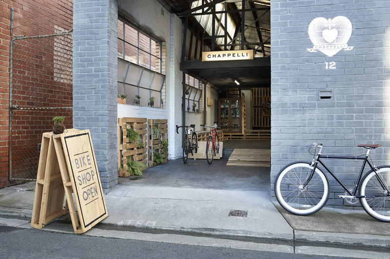 Two wood pallets have been attached with hinges and rope, and then minimally painted to create a simple wood sign letting people know that the bike shop is open.