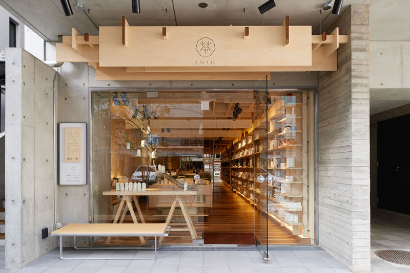 The wood sign with its small simple logo above this tea shop in Japan looks clean and natural against the concrete building it's attached to.