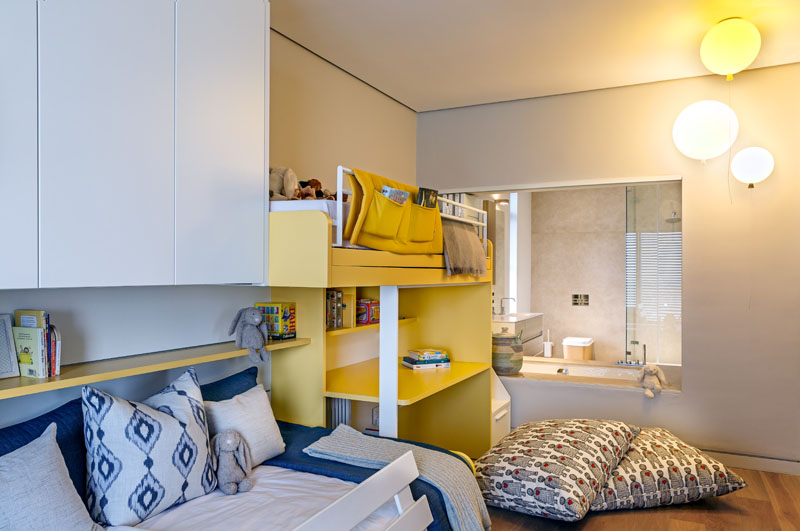 This modern kids bedroom is decorated in blue, white, yellow and balloon light fixtures. A white and yellow bunk bed has a desk below it, and a cut-out in the wall with shutters reveals the ensuite bathroom.