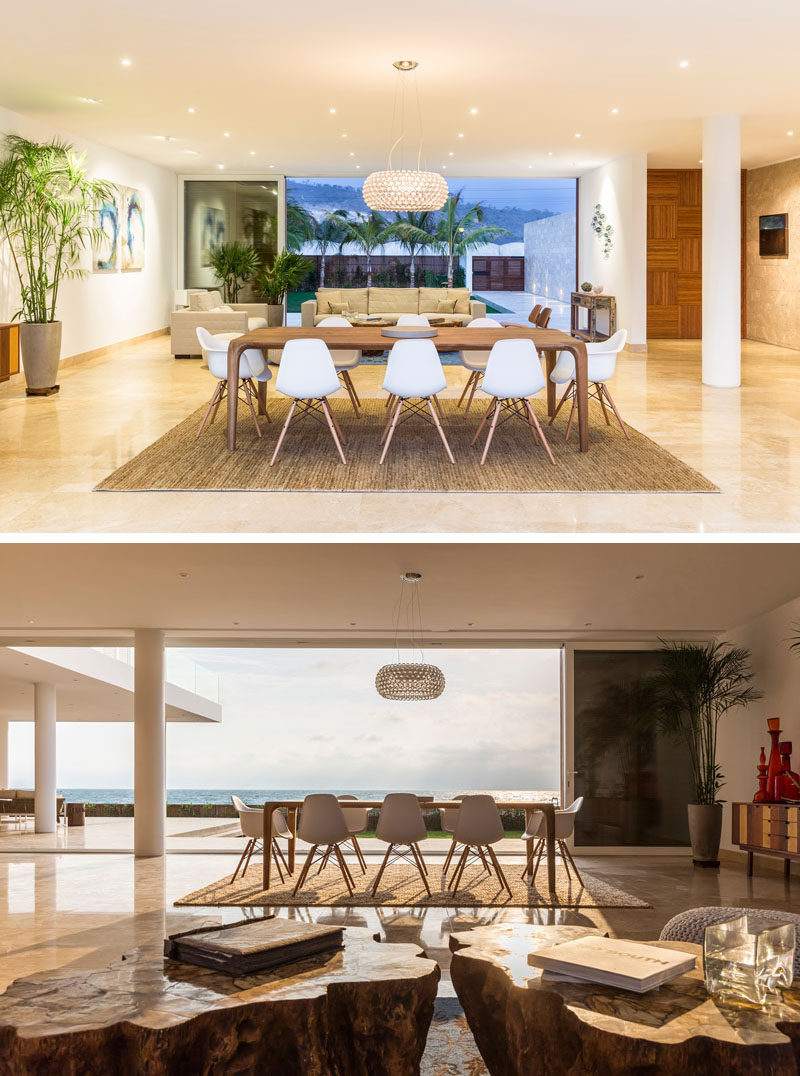 Heading inside this modern beach house, the dining and living room have a breathtaking view of the water. The combination of white, stone, and wood are used again inside the home to create a cohesive design.