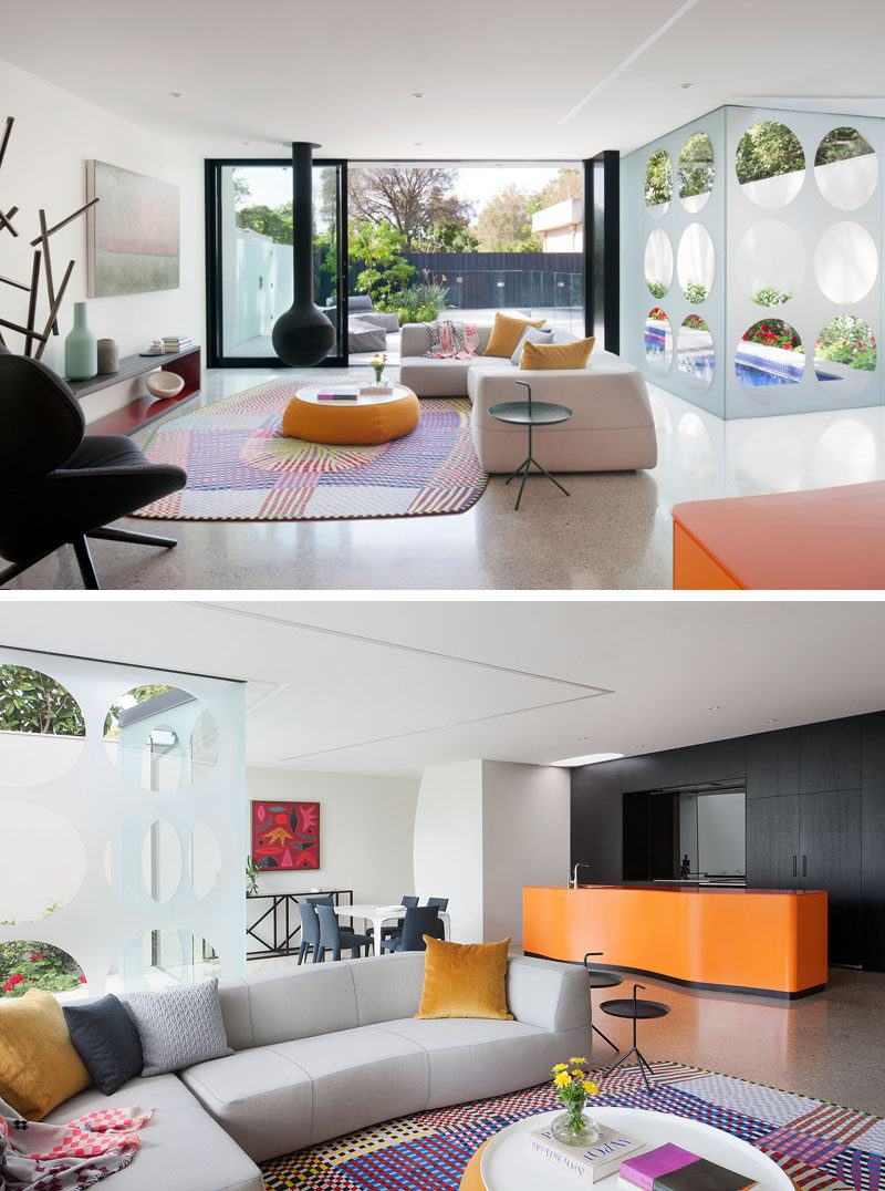 This living room opens up to the patio outside through large black-framed sliding glass doors. To tie in with the black frames, a Bathyscafocus suspended fireplace hangs from the ceiling. The living room is also open to the kitchen and the dining area.