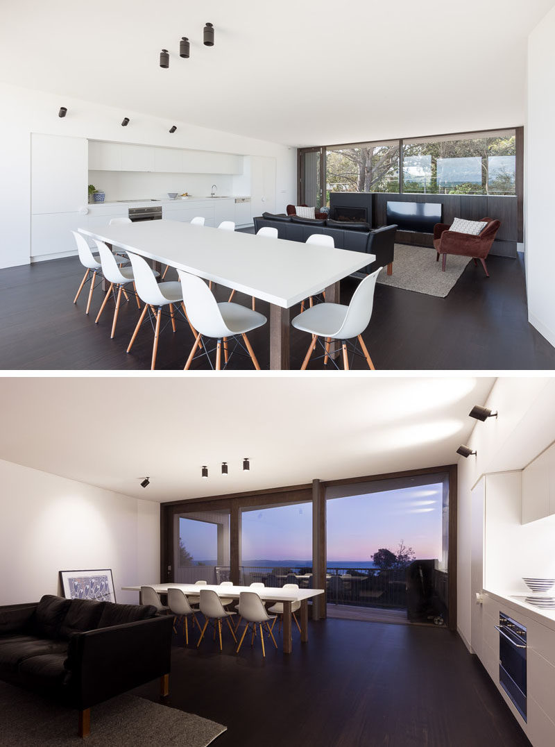 In this modern beach house, the living room and dining area share the same space, but face away from each other to create separation. The living room faces the front of the home, while the dining area faces the back of the home. The minimalist white kitchen keeps the space uncluttered and functional.