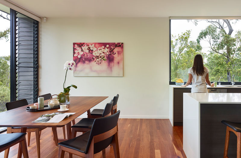 This modern dining room features a simple look, with the wood and black upholstered dining set complimenting the rich wood flooring, while a pop of color is added to the dining area with a pink floral painting.