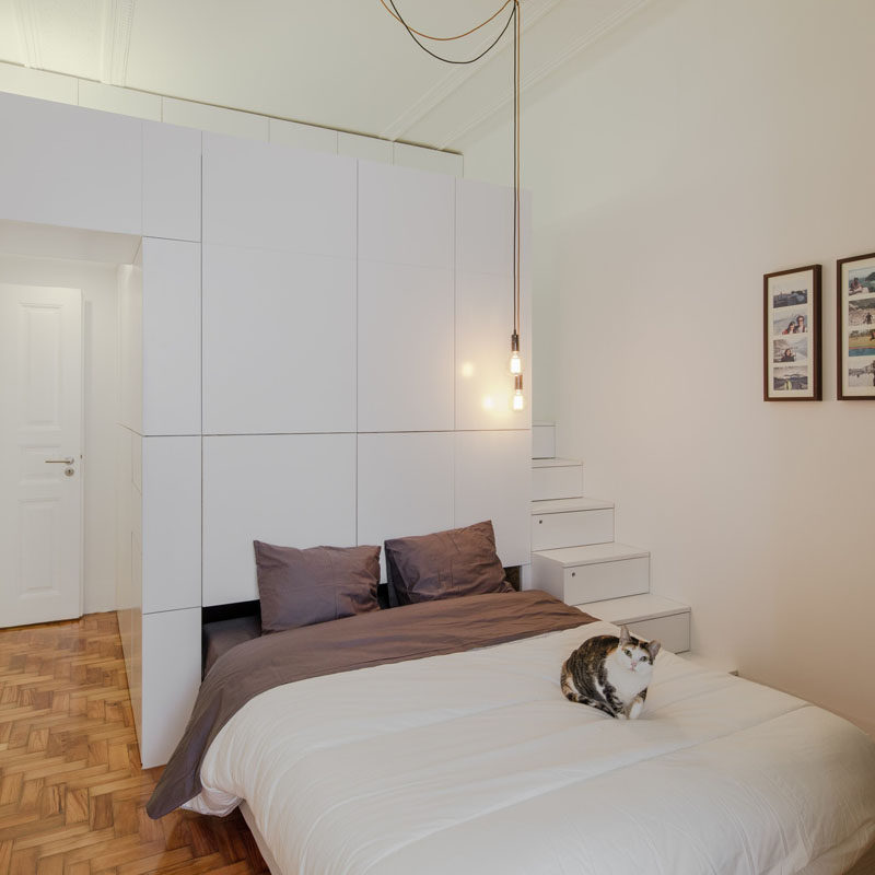 This small modern apartment has a wall of white storage cabinets that allows a pull-out bed to be hidden within it.