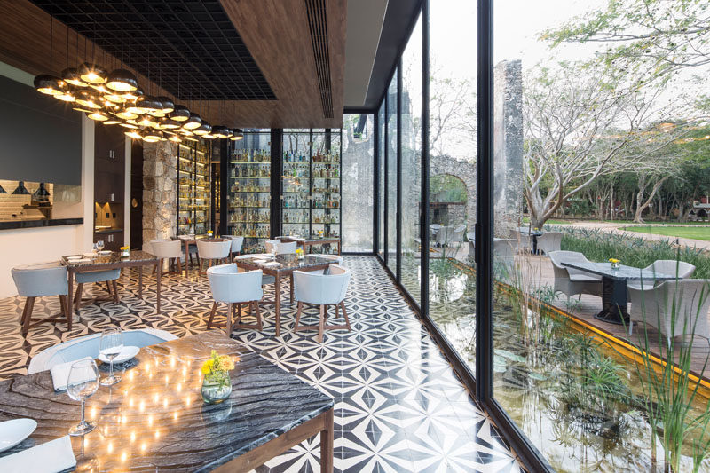 This modern restaurant has a large dining room that looks out onto the surrounding landscape through floor to ceiling windows.