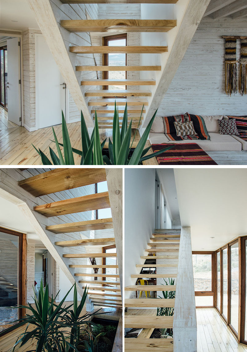 Wood stairs lead up to the upper floor of this modern house, where bedrooms are located. Beneath the stairs is a void in the floor for plants that add greenery to the otherwise light interior.