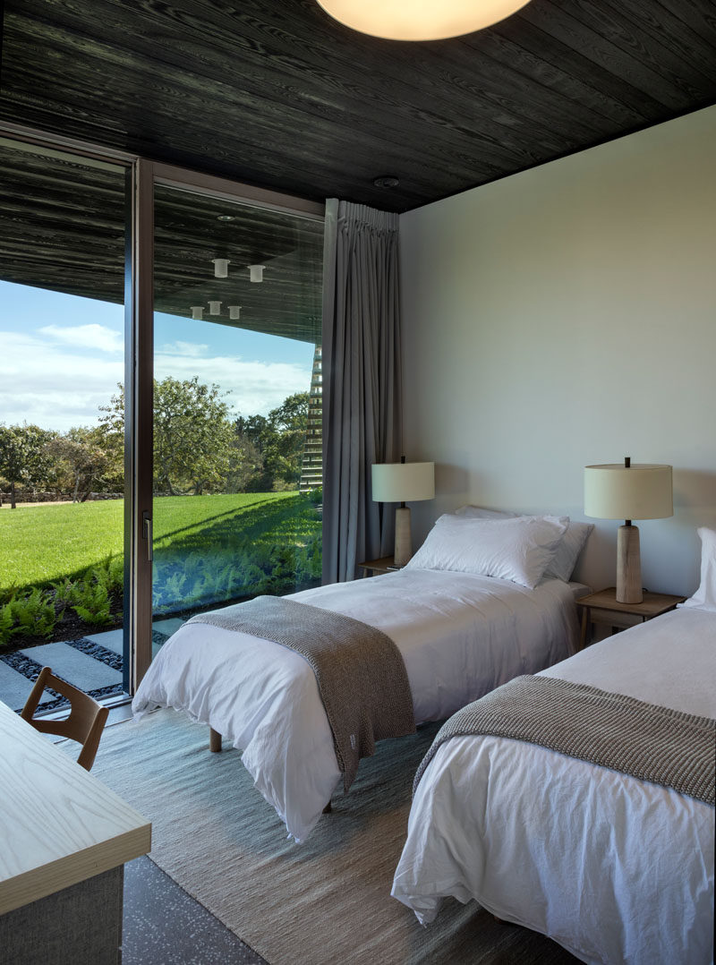 In this modern bedroom, two beds separated by nightstands, have tree views and direct access to the garden.