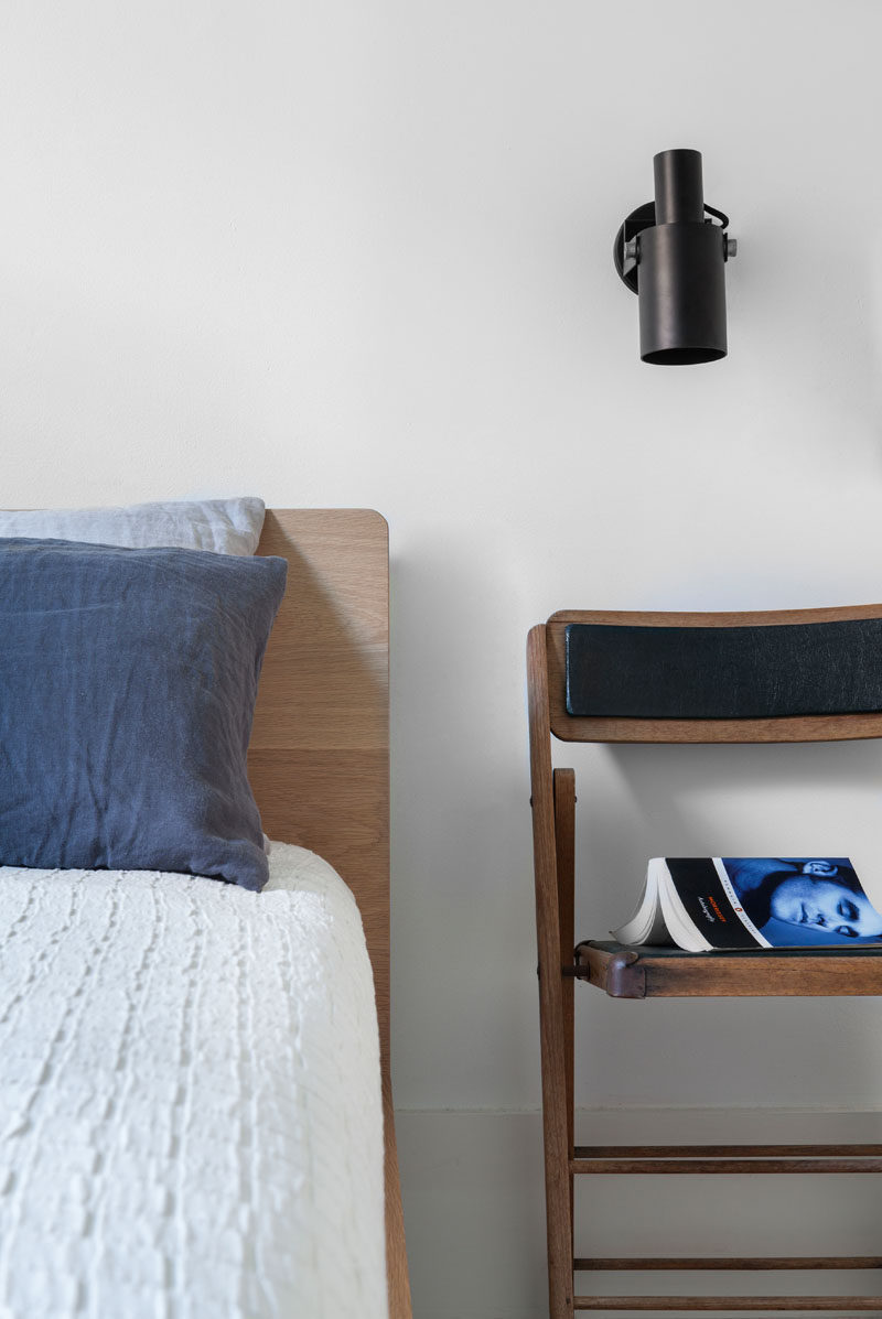 This bedroom has been kept simple in its design with white walls and wood elements, like the bed frame and chair that is being used as a nightstand.