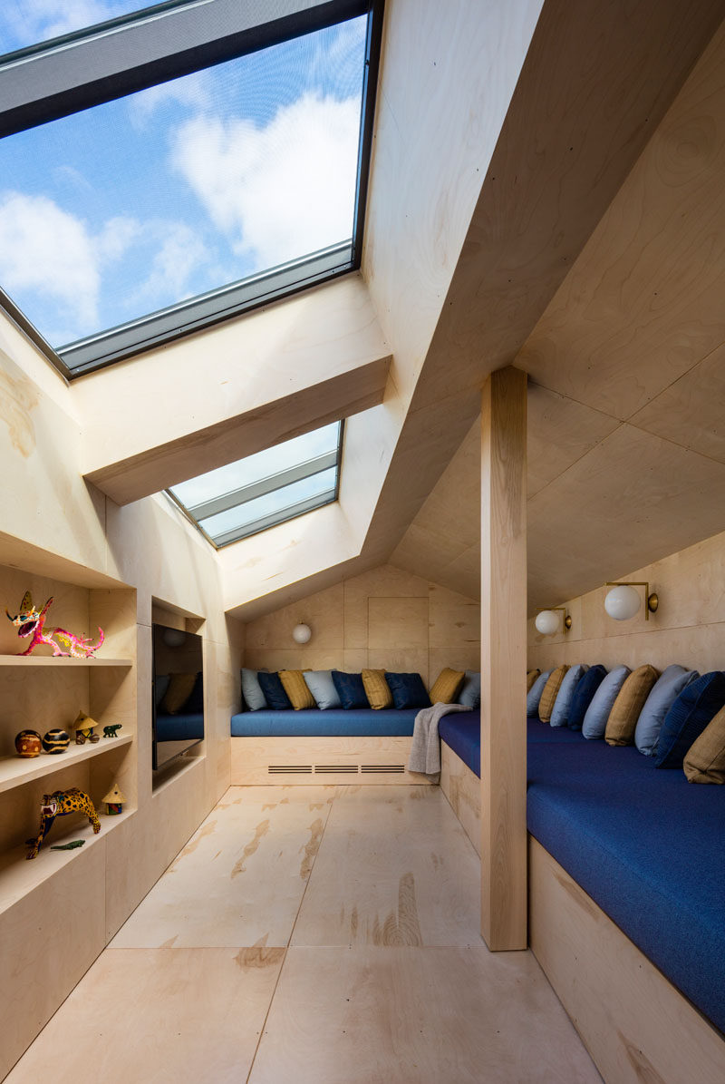 This cozy media room has plenty of skylights and built-in seating with lots of pillows. On the opposite side of the small room is a wood with sections cut-out for shelving and to house the television.