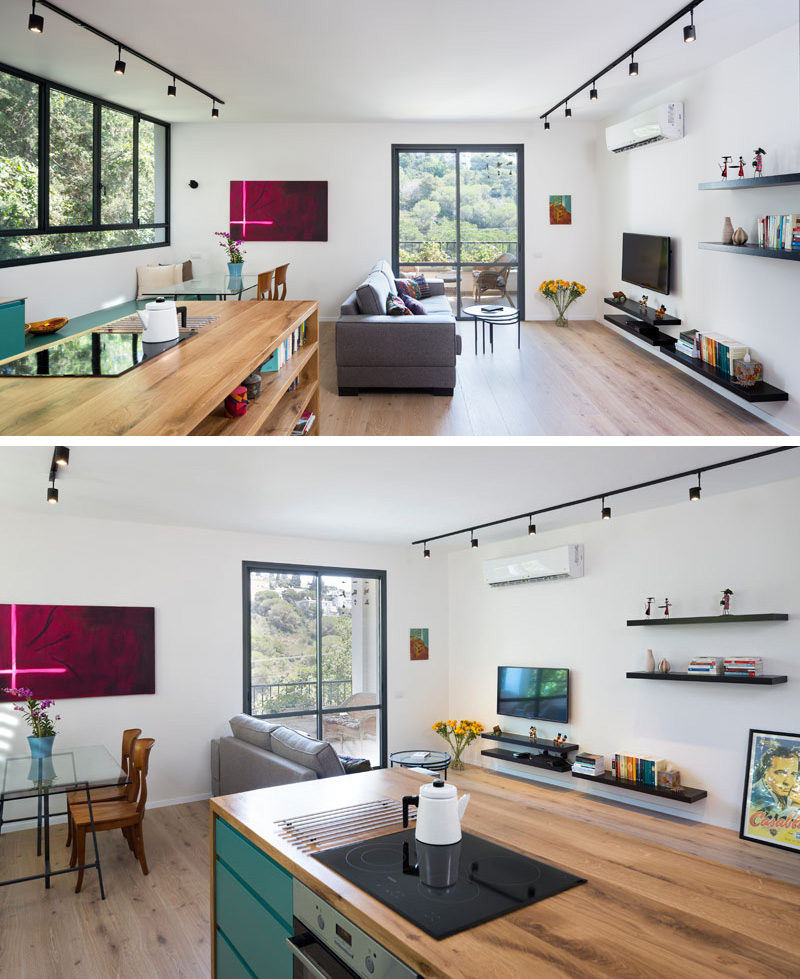 This open plan small modern apartment has a wood island with built-in book shelves the defines the kitchen area, while a gray couch sits in front of the TV wall, which has black track lighting and floating black shelves to allow for extra ornamental displays.