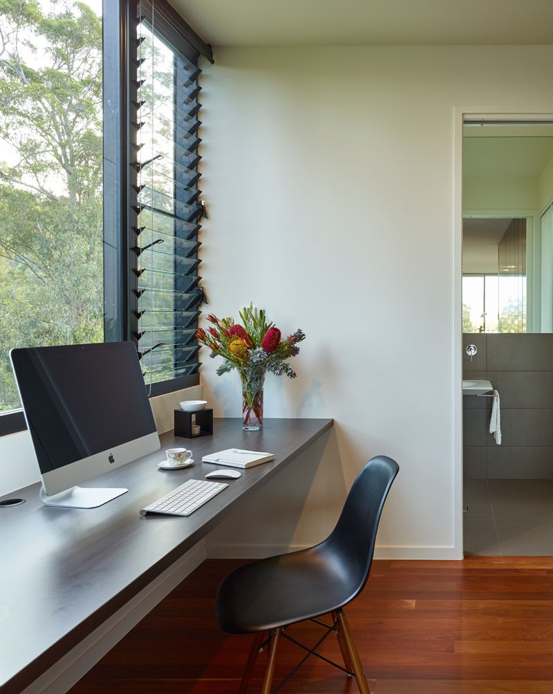 In this hallway to the bathroom, is a small home office with a floating desk. A combination of windows and louvers allows natural light to fill the space.