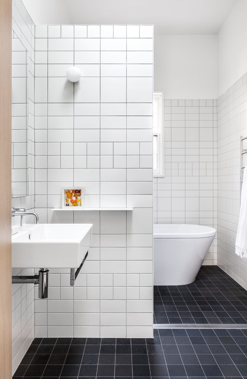 In this modern and simple bathroom, white tiles in different sizes have been used for the walls, while black tiles have been used for the floor.