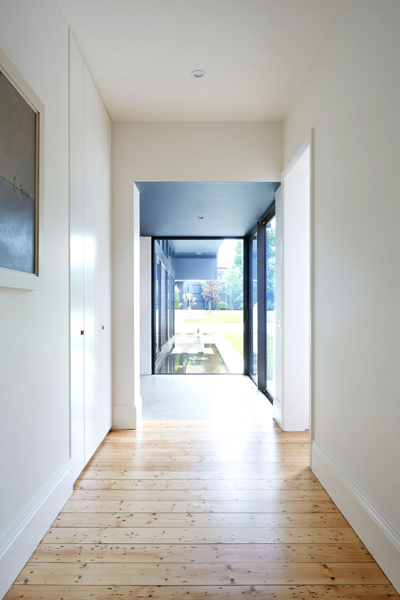 This white hallway has wood and concrete flooring. The wood flooring is from the original house, while the concrete floor is in the new modern extension.