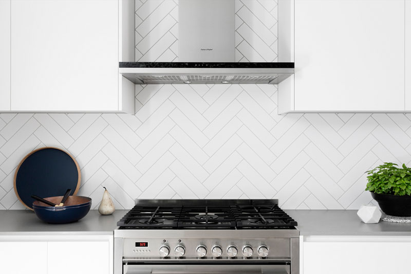 A herringbone backsplash with light grout, white cabinets and stainless steel appliances, brings texture and pattern into this modern kitchen.