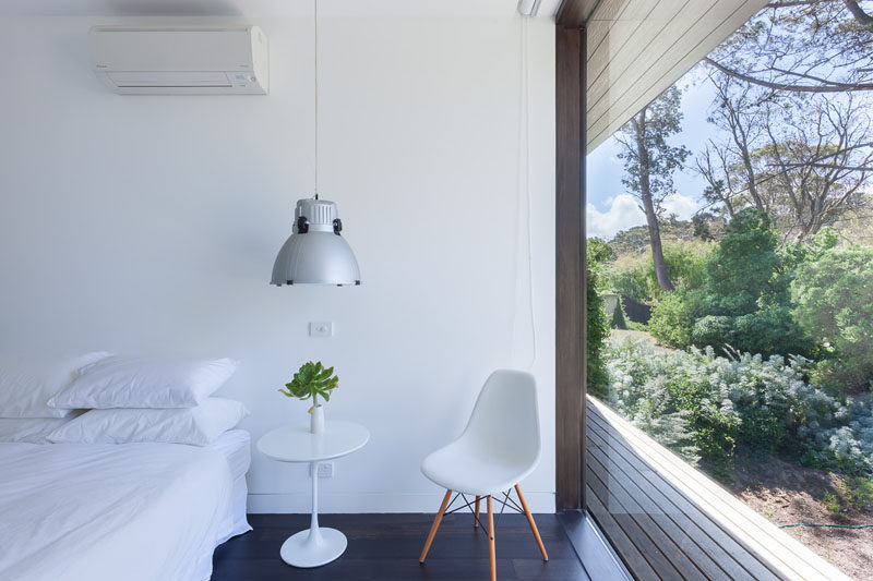 This modern bedroom is simply decorated in white with dark hardwood floors, this room with a large floor to ceiling window, has a beautiful view of the vegetation at the front of the house.