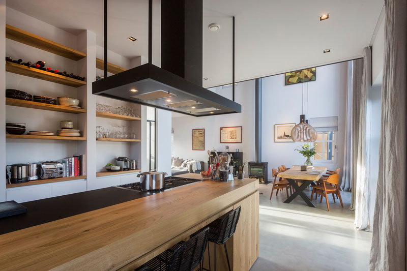 This modern kitchen has light wood island with a built-in stove and space for seating is the focal point in this room. Exposed wood shelving on the wall makes housewares easy to reach.