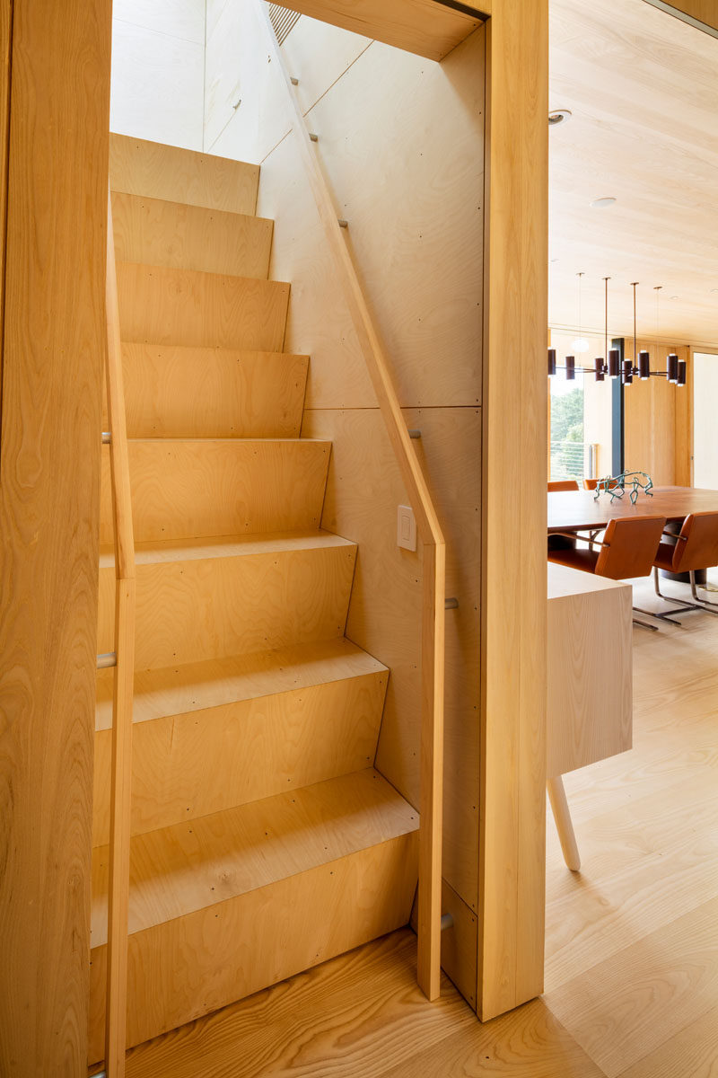 This wooden staircase (also known as a ships ladder staircase) leads to a cozy media room.