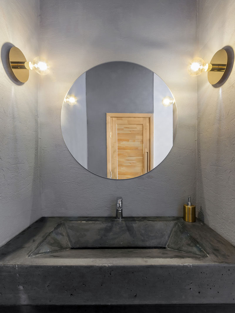 In this modern and simple bathroom, a custom concrete sink fits the space perfectly, gold sconces grace the wall and the round mirror matches the shape of the sconces.
