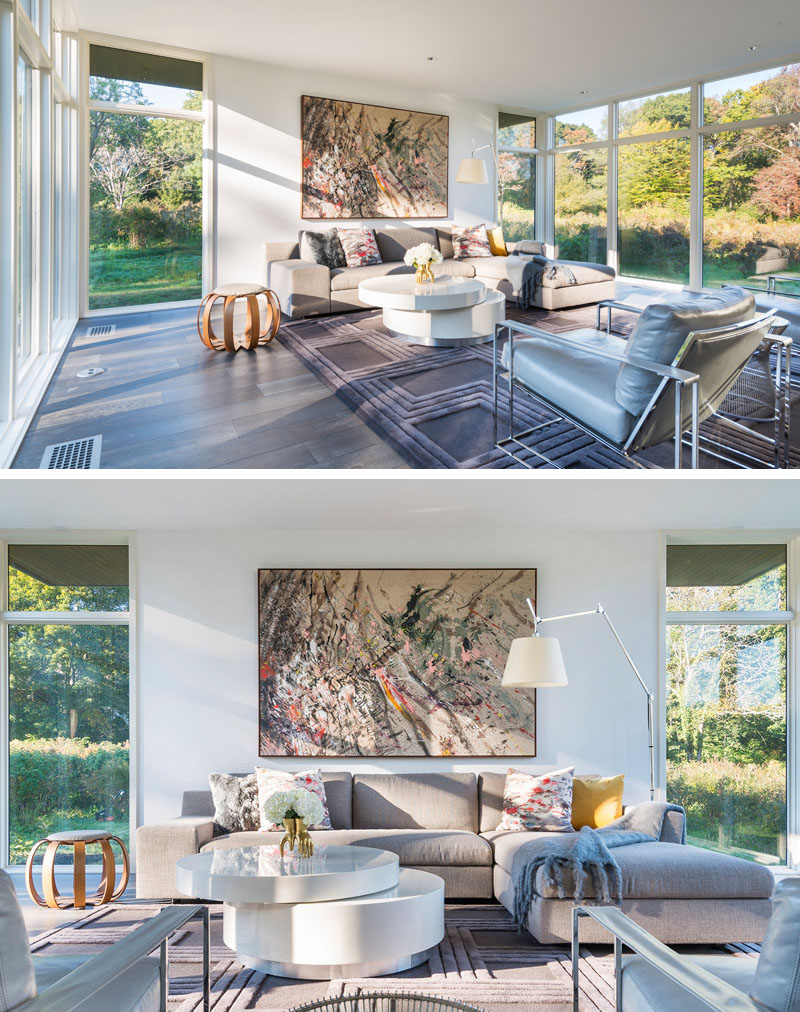 In this modern living room, views of outside can be enjoyed on the L-shaped upholstered sofa and grey leather arm chairs. A large graphic mounted art piece compliments the tones and hues use in the room.